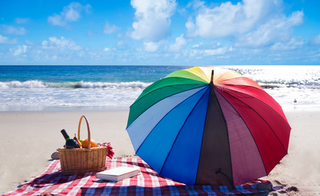 Picnic background with basket, fruits, book and umbrella by the ocean