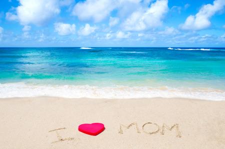 Sign I love mom on the sandy beach next to ocean Stock Photo