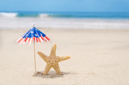 Patriotic USA background with starfishes and decorations on the sandy beach photo
