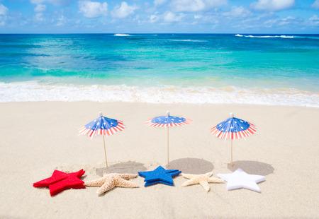 julio: Fondo patriótico EE.UU. con estrellas de mar y decoraciones en la playa de arena