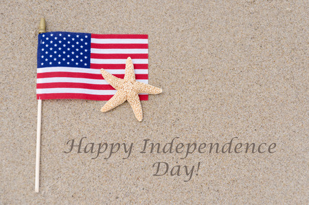 Happy Independence Day USA background with flag on the sandy beach (4th of july holiday concept) Standard-Bild