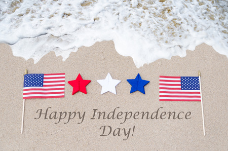 white day: Happy Independence Day USA background with flag on the sandy beach (4th of july holiday concept) Stock Photo