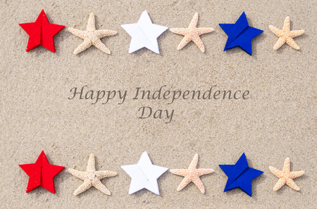 celebration day: Happy Independence Day USA background with starfishes, red, blue and white stars on the sandy beach (4th of july holiday concept)