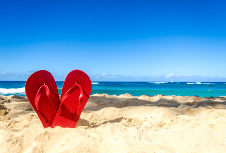 flip flops on the beach: Red flip flops in heart shapes on the sandy beach in Hawaii, Kauai (romantic concept) Stock Photo