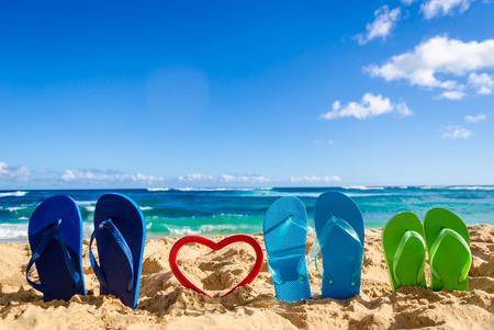 Flip flops with heart shape on the sandy beach in Hawaii, Kauai (romantic concept) Stock Photo