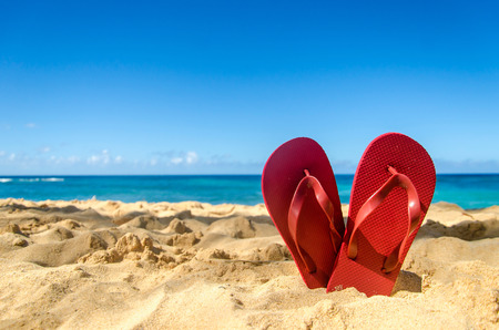 a pair of: Red flip flops in heart shape on the sandy beach in Hawaii, Kauai (romantic concept)