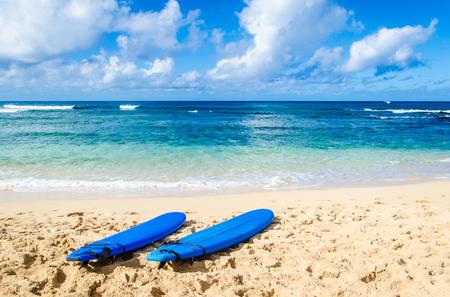 surf board: Two Surfboards on the sandy Poipu beach in Hawaii, Kauai Stock Photo