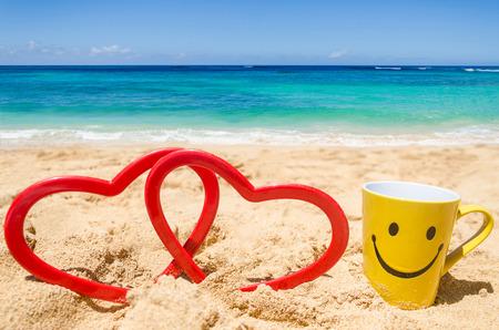 carita feliz: Taza feliz de la cara con forma de coraz�n en la playa de arena
