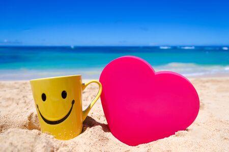carita feliz: Taza feliz de la cara con forma de coraz�n en la playa en Hawai Foto de archivo