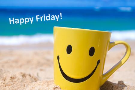 """Het gezicht van Smiley mok op het zandstrand en het teken """"Happy vrijdag"""""""