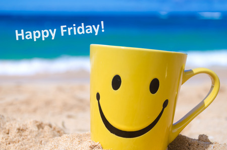 Smiley face mug on the sandy beach and sign Happy friday