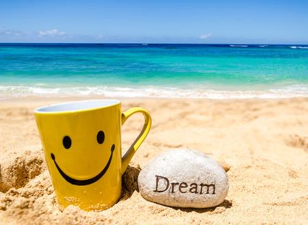 """cara de alegria: Taza feliz de la cara y el signo """"Dream"""" en la playa de arena Foto de archivo"""
