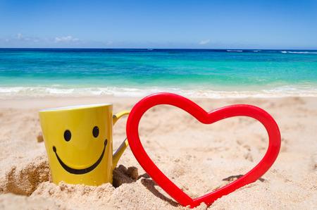 carita feliz: Taza feliz de la cara y de la forma del coraz�n en la playa en Hawai Foto de archivo
