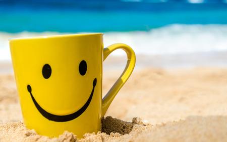 carita feliz: Taza feliz de la cara en la playa de arena