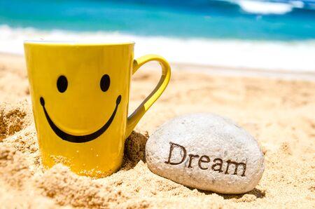 """cara de alegria: Taza feliz de la cara y el signo """"sue�o"""" en la playa de arena"""