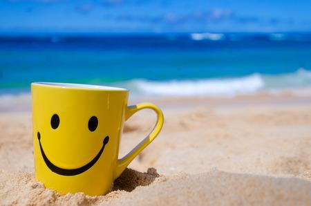 cara de alegria: Taza feliz de la cara en la playa de arena