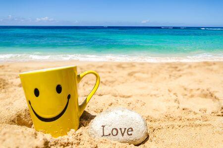"""cara de alegria: Taza feliz de la cara y el signo de """"amor"""" en la playa de arena Foto de archivo"""