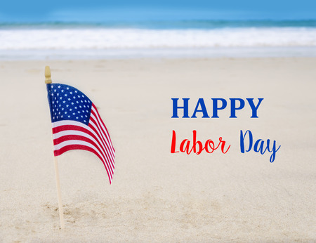 Labor Day USA background with American flag on the sandy beach