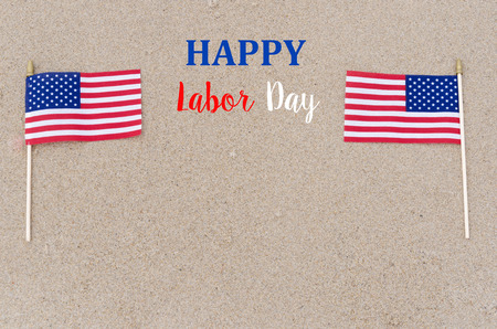 Happy Labor Day background with flags on the sandy beach - USA holidays concept