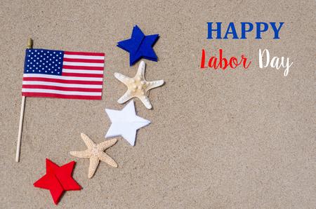 Dag van de Arbeid achtergrond met vlag en wit, blauw en rode sterren en zeesterren op het strand - USA vakantie concept Stockfoto