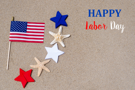 presidents' day: Labor Day background with flag and white, blue and red stars and starfishes on the sandy beach - USA holidays concept Stock Photo