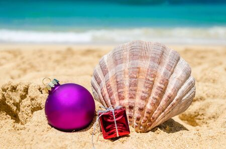 beach happy new year: Merry Christmas and Happy New Year background with Seashell, gift and a ball on the tropical beach near ocean in Hawaii Stock Photo