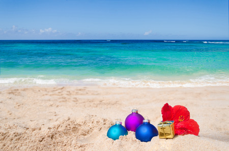 beach happy new year: Merry Christmas and Happy New Year background with gift, flower and balls on the tropical beach near ocean in Hawaii Stock Photo