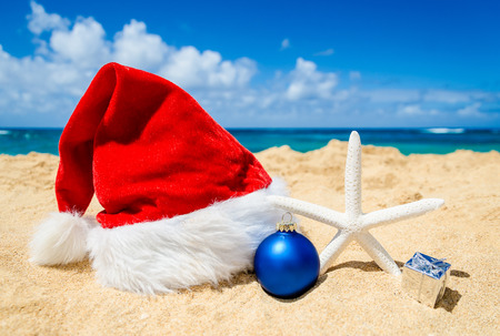 beach happy new year: Merry Christmas and Happy New Year background with Santa Claus Hat and staerfish in the beach near ocean in Hawaii Stock Photo