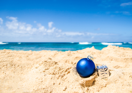 beach happy new year: Merry Christmas and Happy New Year background with gift and ball on the tropical beach near ocean in Hawaii
