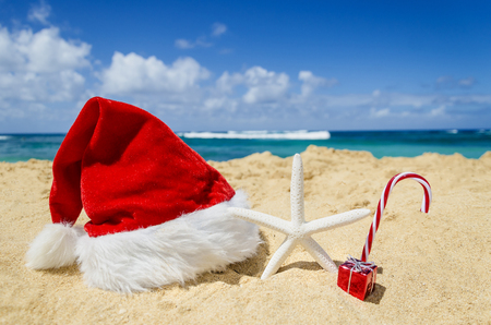 Merry Christmas and Happy New Year background with Santa Claus Hat and starfish on the tropical beach near ocean in Hawaii Stock Photo