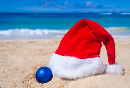 beach happy new year: Merry Christmas and Happy New Year background with Santa Claus Hat and balls on the tropical beach near ocean in Hawaii