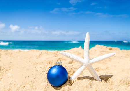 beach happy new year: Merry Christmas and Happy New Year background with starfish and ball on the tropical beach near ocean in Hawaii