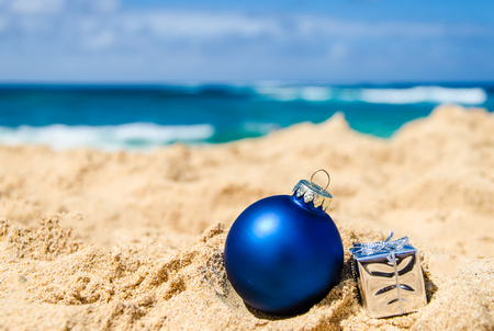arena: Feliz Navidad y Feliz Año Nuevo fondo con el regalo y la bola en la playa tropical cerca del océano en Hawai
