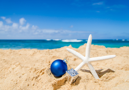 beach happy new year: Merry Christmas and Happy New Year background with starfish, gift and ball on the tropical beach near ocean in Hawaii