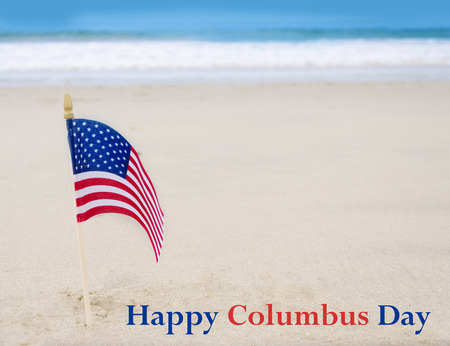 Columbus Day background with American flag on the sandy beach
