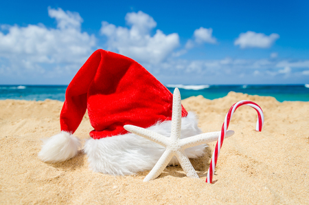 Merry Christmas and Happy New Year background with Santa Claus Hat, candy and starfish on the tropical beach near ocean in Hawaii