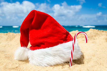 beach happy new year: Merry Christmas and Happy New Year background with Santa Claus Hat and candy on the tropical beach near ocean in Hawaii