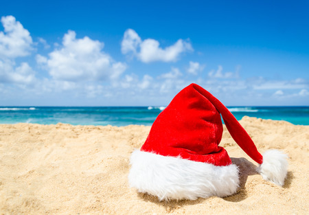 beach happy new year: Merry Christmas and Happy New Year background with Santa Claus Hat on the tropical beach near ocean in Hawaii