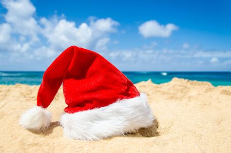 Merry Christmas and Happy New Year background with Santa Claus Hat on the tropical beach near ocean in Hawaii