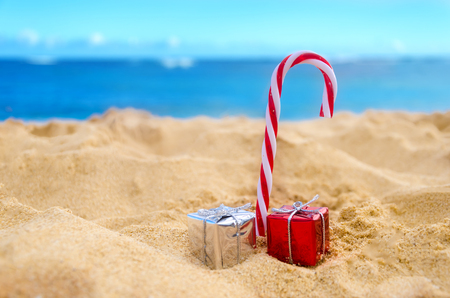 beach happy new year: Merry Christmas and Happy New Year background, candy and gifts on the tropical beach near ocean in Hawaii Stock Photo