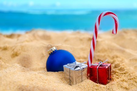 beach happy new year: Merry Christmas and Happy New Year background, Christmas ball, candy and gifts on the tropical beach near ocean in Hawaii