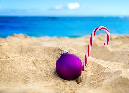 beach happy new year: Merry Christmas and Happy New Year background, candy and Christmas ball on the tropical beach near ocean in Hawaii