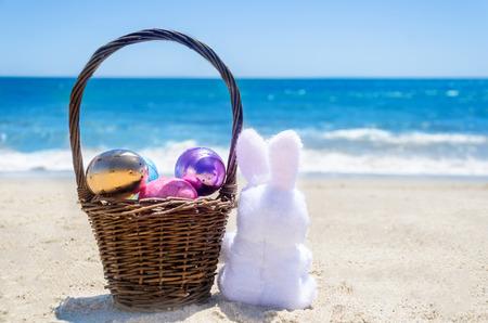 Easter bunny with  basket and color eggs on the sandy beach near ocean Stock Photo