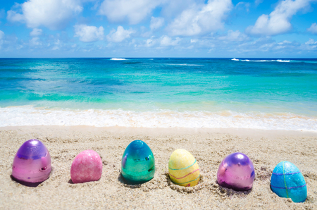 Easter color eggs on the sandy beach near ocean