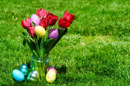Easter Colorful eggs  and bright red tulips on the green grass background - spring mood Stok Fotoğraf