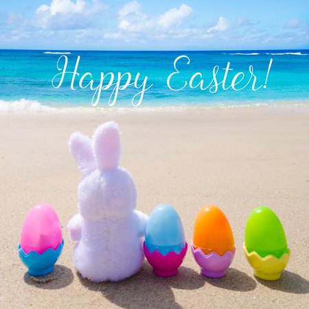 Easter bunny and color eggs on the sandy beach by the ocean - square photo