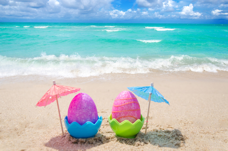 Two easter eggs with cocktail umbrella on the sandy beach