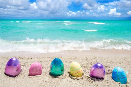 Easter color eggs on the sandy beach near ocean