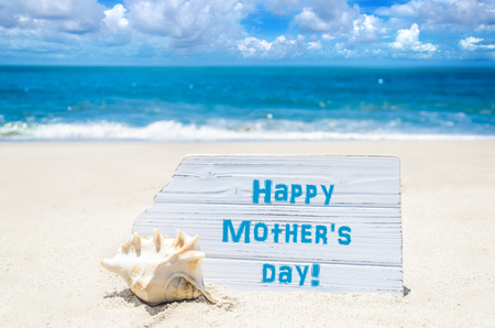customizable: Happy mothers day background with seashell on the sandy beach near the ocean