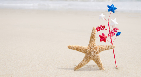 Independence Day USA background  background with starfishe and decorations on the sandy beach near the oceanAmerican patriotic concept Stock Photo